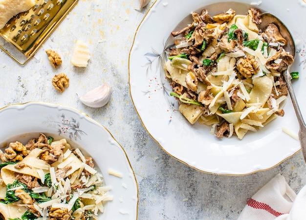 Servieren von hausgemachten pappardelle-nudeln mit champignons und parmesankäse