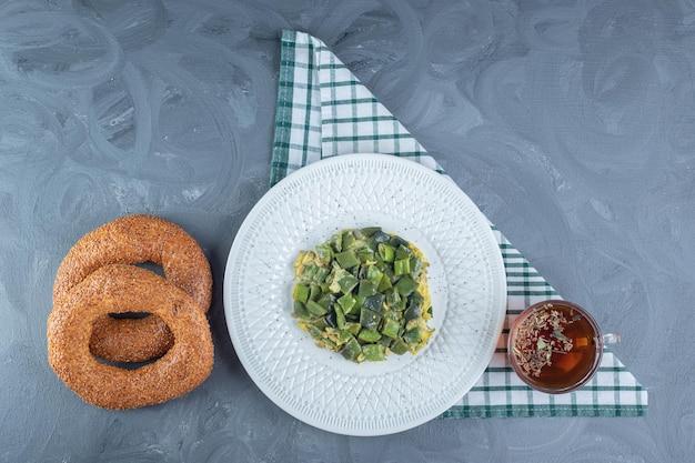 Servieren von mit eiern gekochten bohnenhülsenfrüchten neben einer tasse tee und zwei bagels auf marmoroberfläche.
