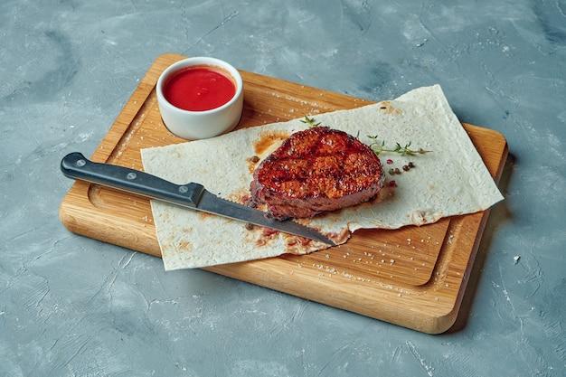 Servieren von rindersteak gekocht im grill in gewürzen auf holzbrett auf grauer oberfläche