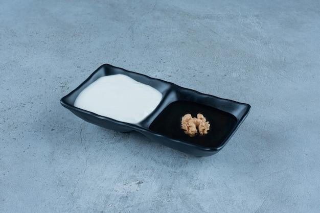 Servierplatte mit portionen sahne und honig auf marmor.