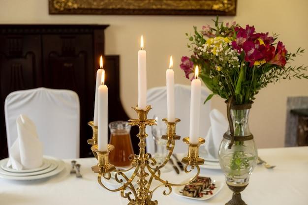 Serviert bankett-restauranttisch mit kandelaber brennenden kerzen, gläsern, servietten und blumenvase, selektiver fokus