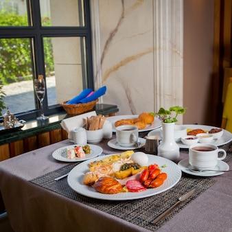Serviert frühstückswürste, gekochtes ei, omelett, croissant in tellern und eine tasse tee auf dem tisch