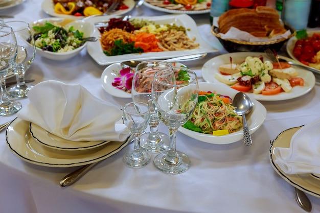Serviert für bankett. weingläser mit servietten, gläsern und salaten.