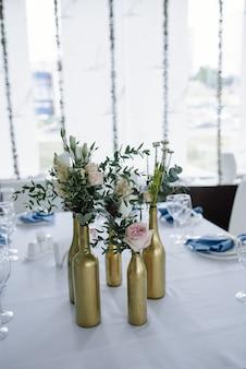 Serviert für hochzeitsbankett tisch in blau weiß. hochzeitsdekoration. blaue serviette mit blume auf einem weißen teller. goldene flaschen sind vasen für blumen.