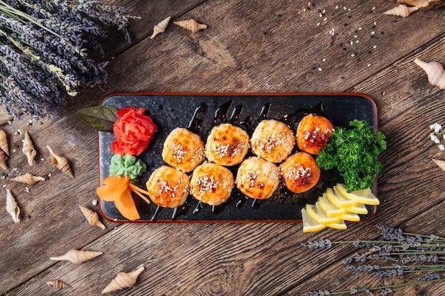 Serviert gebackene sushi-rollen nach amerikanischer art auf teller