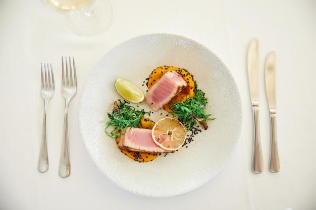 Serviert leckeres thunfischgericht mit zitronenscheibe und sauce