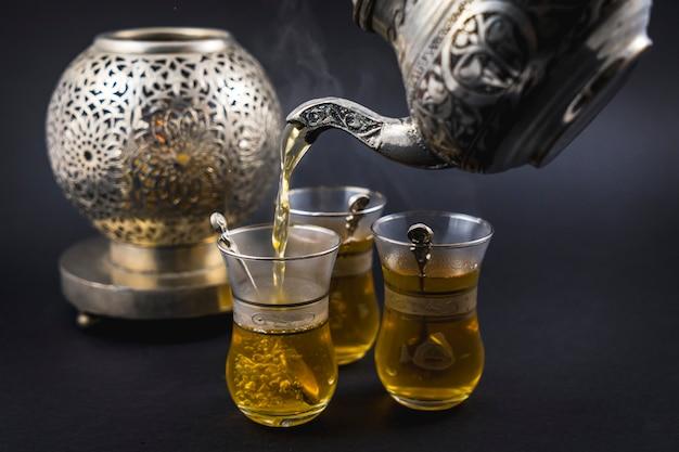 Serviert maurischen tee aus einer metallschale auf drei gläser