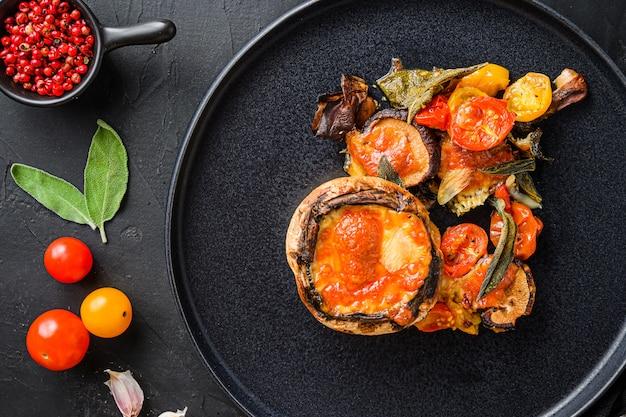 Serviert portobello-pilze, gebacken und gefüllt mit zutaten cheddar-käse, kirschtomaten und salbei auf schwarzem teller über schwarzem hintergrund draufsicht.