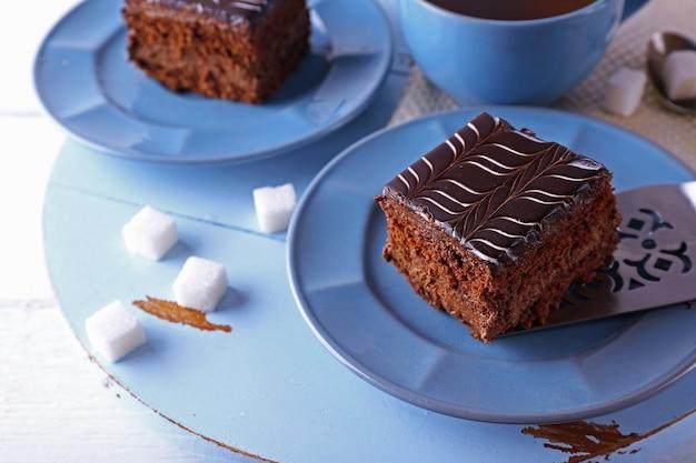 Serviert tisch mit einer tasse tee und schokoladenkuchen auf blauen tellern in nahaufnahme