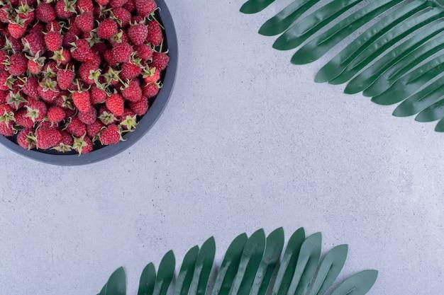 Serviertablett voller himbeeren neben dekorativen blättern auf marmorhintergrund. foto in hoher qualität