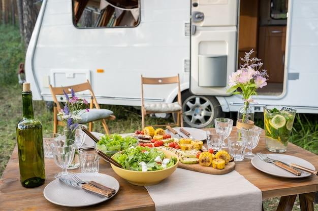 Servierter tisch mit hausgemachten speisen und getränken gegen haus auf rädern