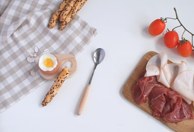 Serviertes frühstück gekochtes ei im hölzernen eierbecher
