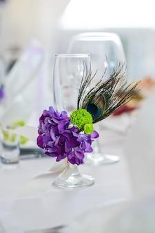 Serviertisch mit tellern, weißen servietten und gläsern mit lila blüten, abendessen im restaurant