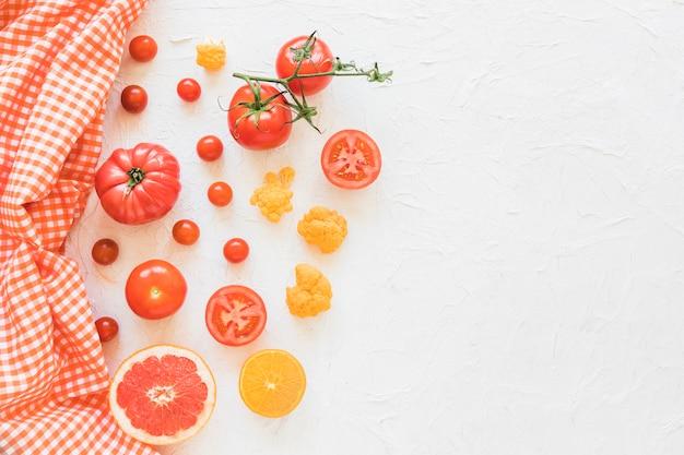 Serviette mit gemüse und früchten auf weißem strukturiertem hintergrund