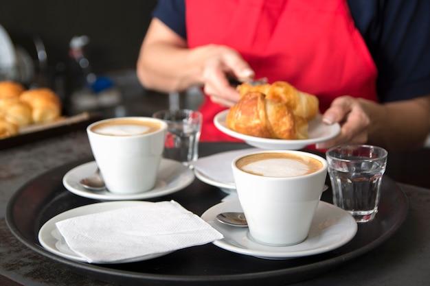 Serving zwei kaffeetassen vor der kellnerin platzieren croissant in der platte