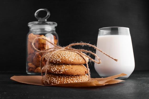 Sesam-keksbrötchen auf einem stück papier, serviert mit einem glas milch.