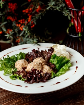 Sesamkugeln dienten auf oberseiten des kopfsalates in der weißen platte
