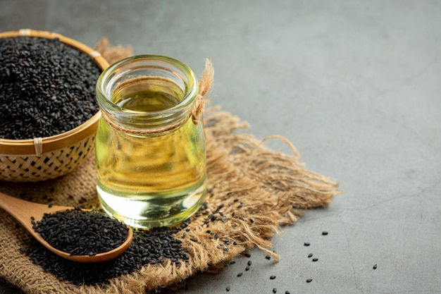 Sesamöl und roher schwarzer sesam auf dunklem hintergrund
