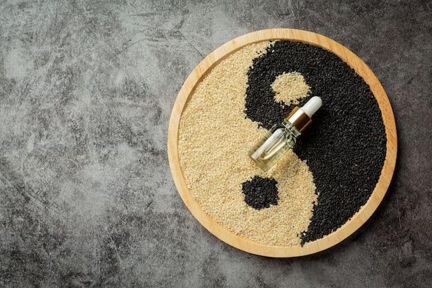 Sesamöl und sesamsamen auf dunklem hintergrund