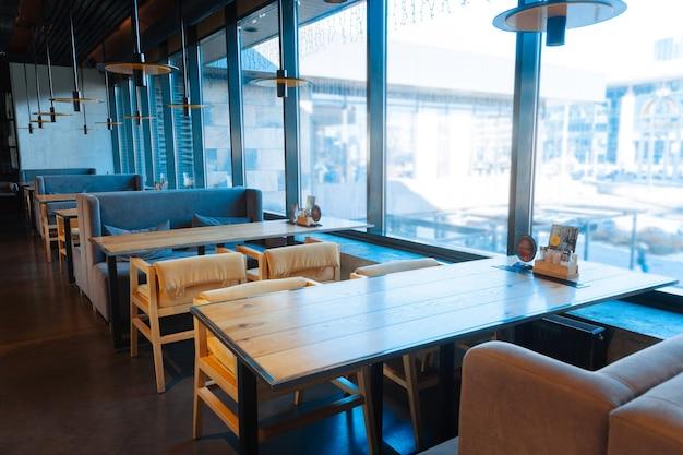 Sessel und sofas. bequeme sessel und sofas in der nähe des tisches im geräumigen restaurant