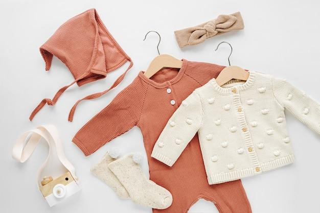 Set aus babyspielanzug, hut, haarband und strickpullover auf weißem bett. mode babykleidung und accessoires. flache lage, ansicht von oben