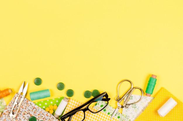 Set aus bunten gelben und grünen stoffen, scheren, knöpfen, garnrollen und gläsern
