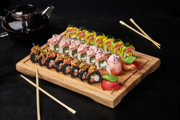 Set aus drei sorten sushi-rollen für zwei personen auf holzbrett