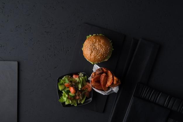 Set aus fast food, cheeseburger mit salat und kartoffeln auf schwarzem hintergrund, ansicht von oben