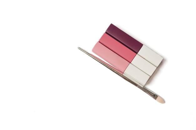 Set aus flüssigen, matten lippenstiften mit verschiedenen farbtönen und pinsel auf weißem hintergrund