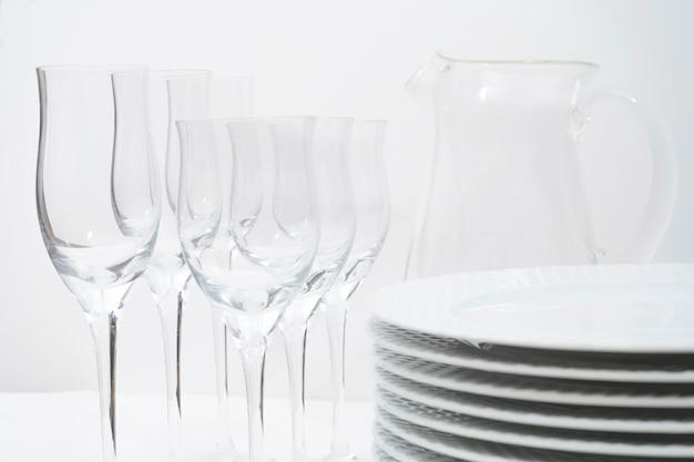 Set aus gestapelten weißen tellern, kristallgläsern und einem glaskrug auf einem weißen tisch.