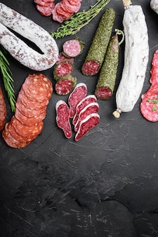 Set aus getrockneter salami, spanischer wurst, scheiben und schnitten auf schwarzem hintergrund, flach mit kopierraum.