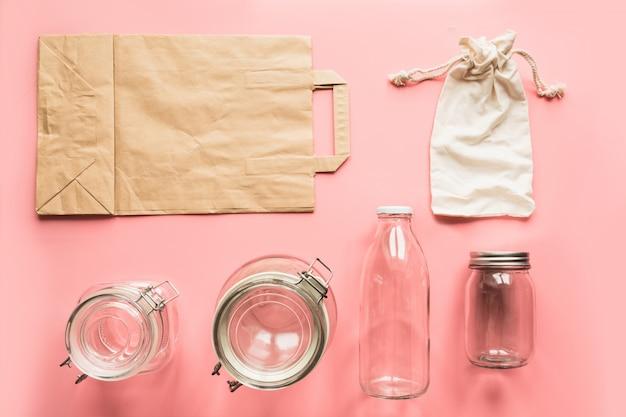 Set aus gläsern und papiertüte für die lagerung und den einkauf von abfällen.