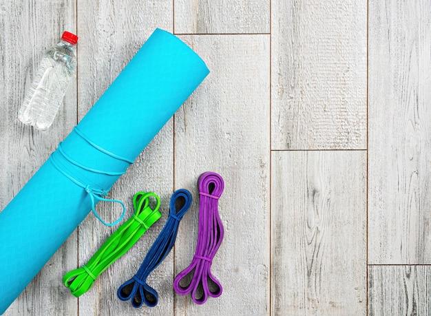 Set aus hellen latex-gummibändern für fitness, yogamatte und eine flasche wasser
