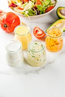 Set aus klassischen salatdressings mit honigsenf, ranch, vinaigrette, zitrone und olivenöl auf weissem marmortisch,