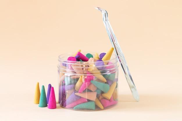 Set aus mehrfarbigen aroma-weihrauchkegeln oder stäbchen in der flasche