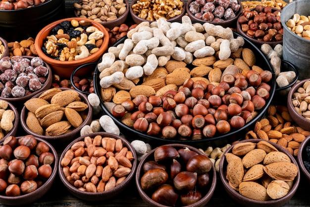 Set aus pekannüssen, pistazien, mandeln, erdnüssen, cashewnüssen, pinienkernen und verschiedenen nüssen und getrockneten früchten in verschiedenen schalen. seitenansicht.
