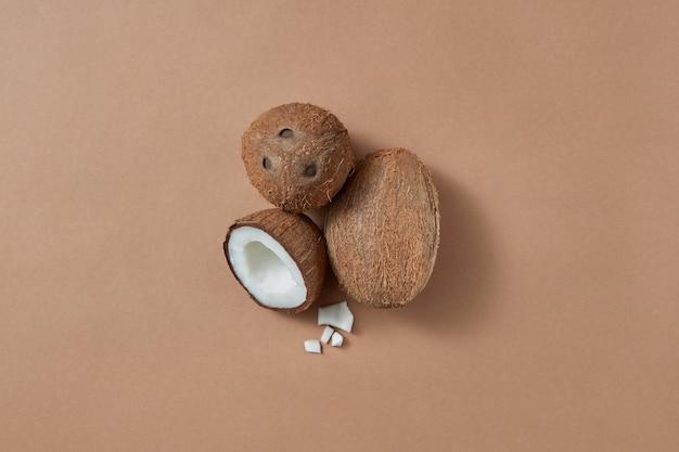 Set aus reifen natürlichen organischen exotischen kokosnussfrüchten zwei ganze und eine hälfte auf braunem hintergrund mit weichen schatten und kopienraum. veganes konzept. ansicht von oben.