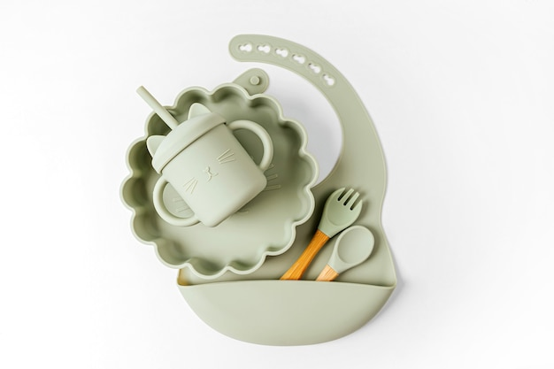 Set aus schalen, tellern und lätzchen für kinder mit trinkbecher in grüner farbe. babygeschirr. ernährungs- und fütterungskonzept.
