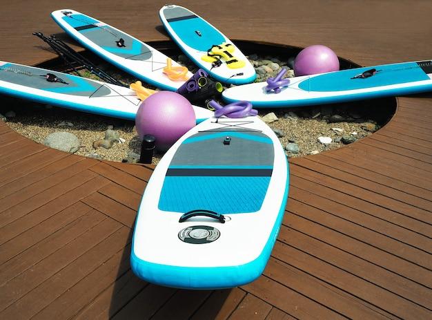 Set aus stand-up-paddleboarding (sup), fitness- und yogageräten für das training am strand