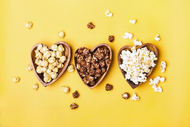 Set aus süßem und gesalzenem popcorn in holzschalen.