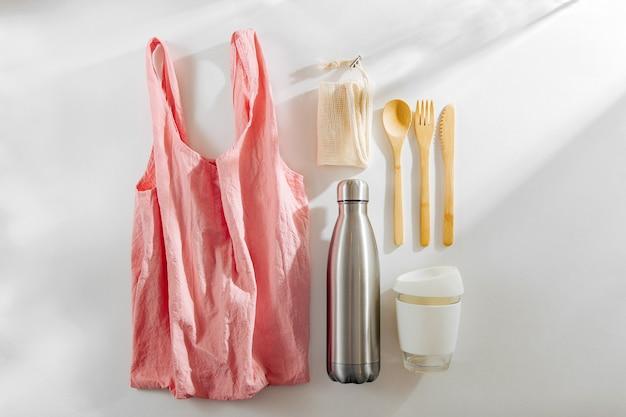 Set aus umweltfreundlichem bambusbesteck, einer wiederverwendbaren kaffeetasse in einer rosa ökotasche und einer wasserflasche.