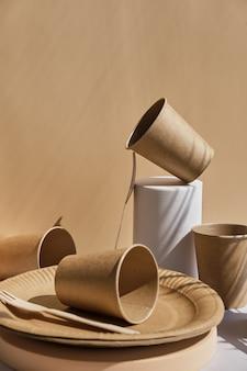 Set aus umweltfreundlichem geschirr, holzgabeln, tellern und gläsern auf trendigen podien und geometrischen sockeln