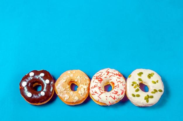 Set aus verschiedenen donuts mit blauer glasur, streusel, mandelkrümel, schokolade und marshmallows