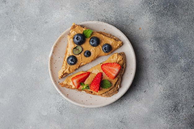 Set aus verschiedenen toasts mit erdnussbutter; honig; minze; erdnuss, blaubeere und erdbeere