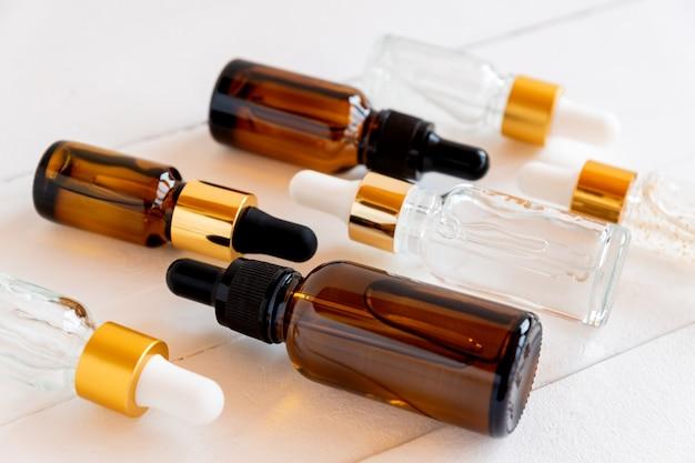 Set aus verschiedenen tropfflaschen mit schönheitspflegeserum, hyaluronsäure und vitaminen auf holzhintergrund. heimkosmetik und spa-konzept