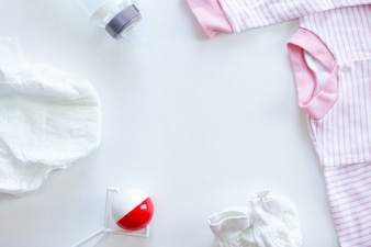 Set Babybedarf auf Tisch: Windel, Sitzsack, Flasche, Anzug