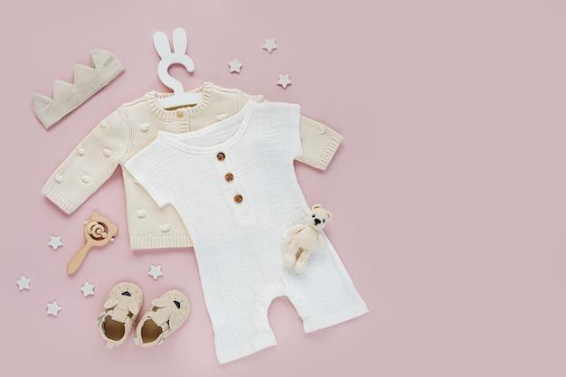Set babykleidung und accessoires auf rosa hintergrund. strickpullover auf süßem kleiderbügel mit weißem body und schuhen, baumwollkrone und spielzeug. mode neugeborenes. flache lage, ansicht von oben