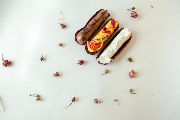 Set bestehend aus drei eclairs mit verschiedenen füllungen und designs. isolieren sie auf einer weißen oberfläche, die mit trockenen rosen verziert wird