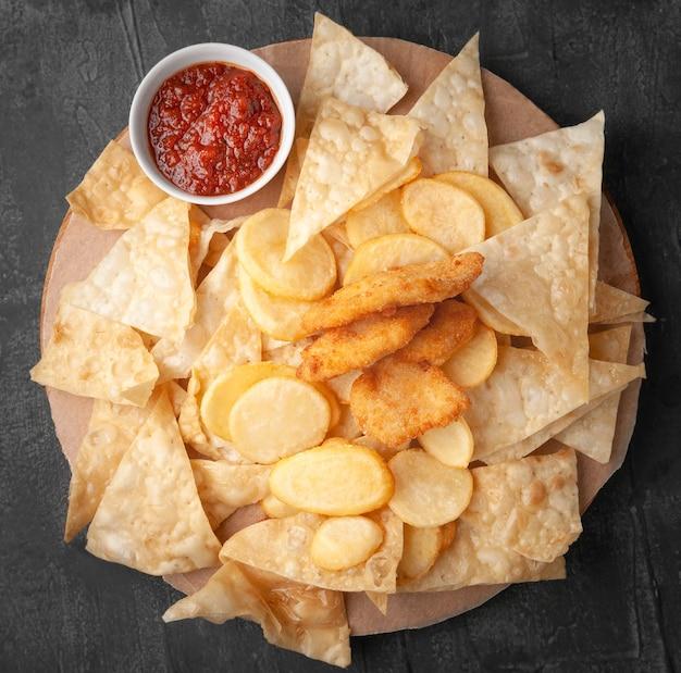 Set biersnacks. bestehend aus nachos-chips, pommes frites und nuggets. mit tomatensauce. auf einem runden holzbrett serviert. sicht von oben. grauer betonhintergrund.