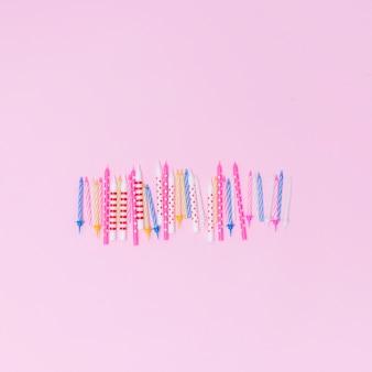 Set bunte kerzen auf rosafarbenem hintergrund